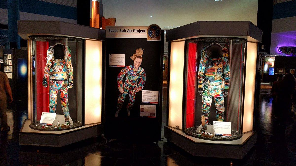 Mujer astronauta mostrando los trajes que hicieron varios niños con cáncer