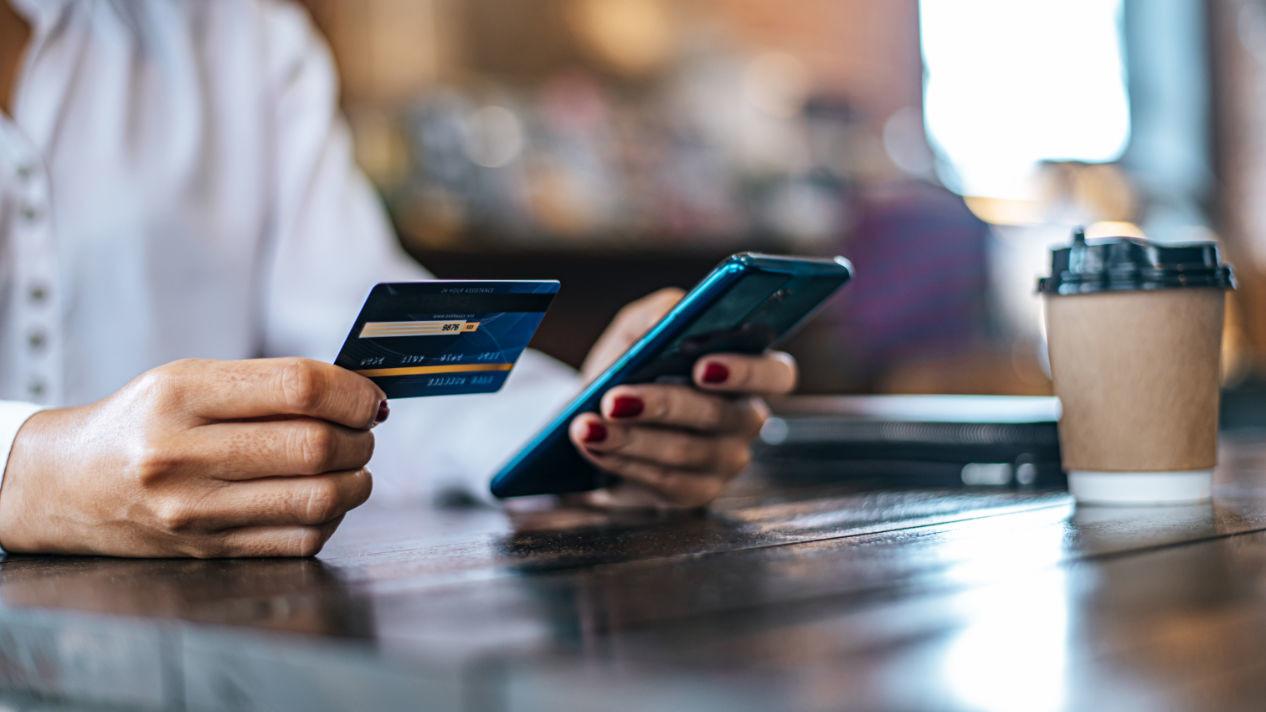 Persona usando tarjeta de debito para pagar